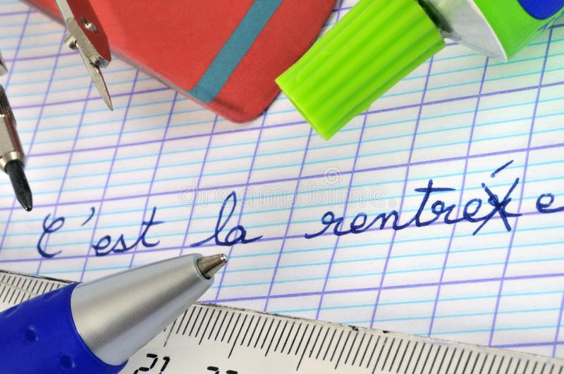 It`s back to school written in French. Close-up on a school notebook on which is written it`s back to school stock illustration
