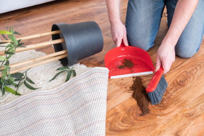Close-up schoonmakende mens die houten vloer met bezem vegen stock afbeeldingen