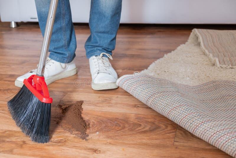 Close-up schoonmakende mens die houten vloer met bezem vegen royalty-vrije stock foto's
