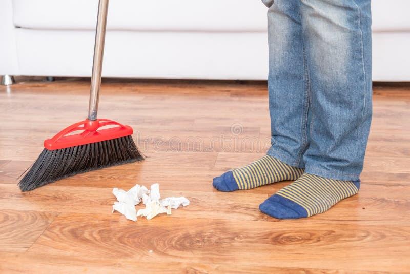 Close-up schoonmakende mens die houten vloer met bezem vegen stock foto's