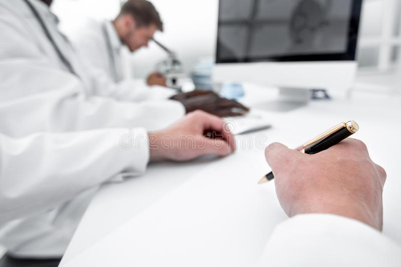 Close-up of the scientist makes a record sitting at the laboratory table. Science and health stock photography