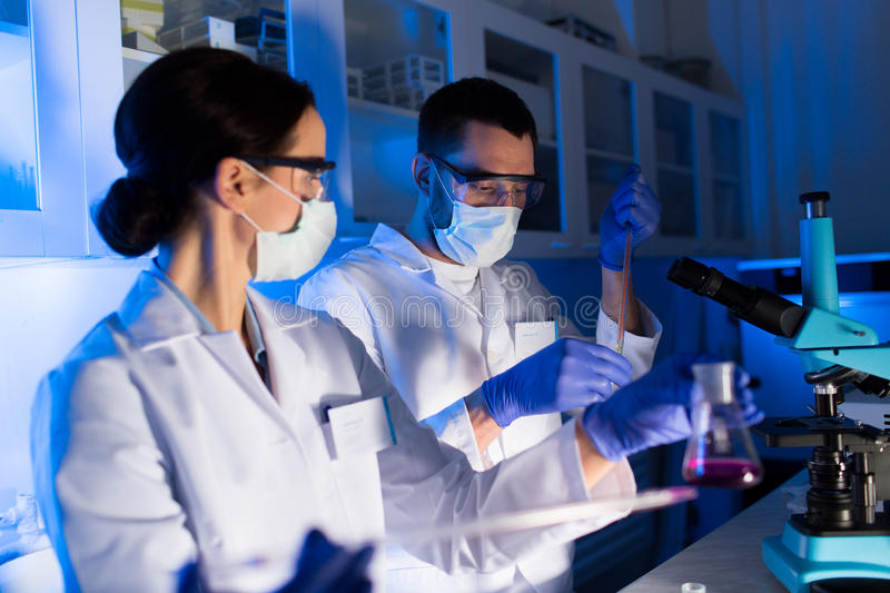 Close up of scientists making test in lab. Science, chemistry, biology, medicine and people concept - close up of young scientists with pipette and flasks making royalty free stock photography