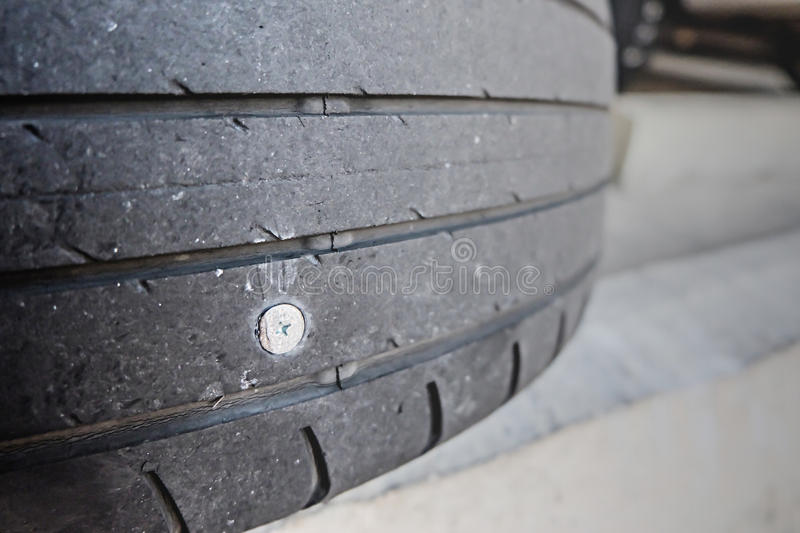 Close up of nail puncturing car tire. Flat tire because the tire. The eternal nemesis royalty free stock image