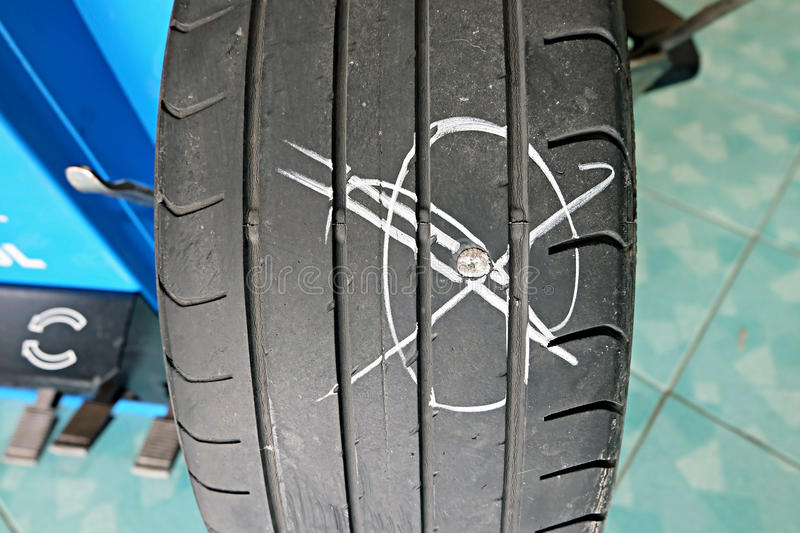 Close up of nail puncturing car tire. Flat tire because the tire. The eternal nemesis stock image