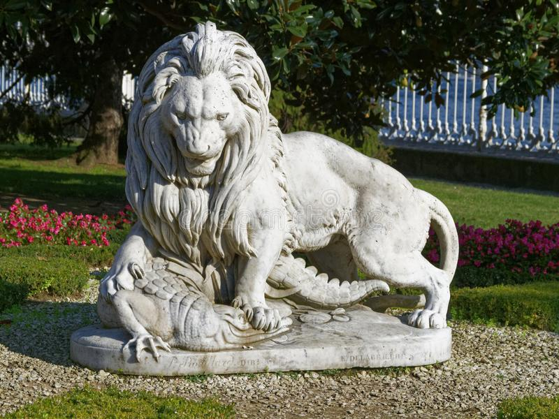 Close up of the sculpture of a lion fighting with a crocodile in the garden of Dolmabahce Palace. stock image