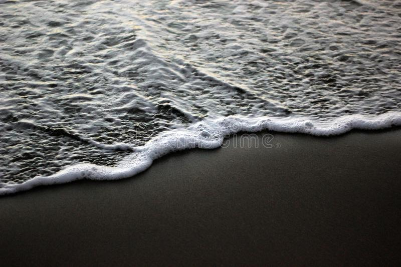 Sea foam on black sand stock photos