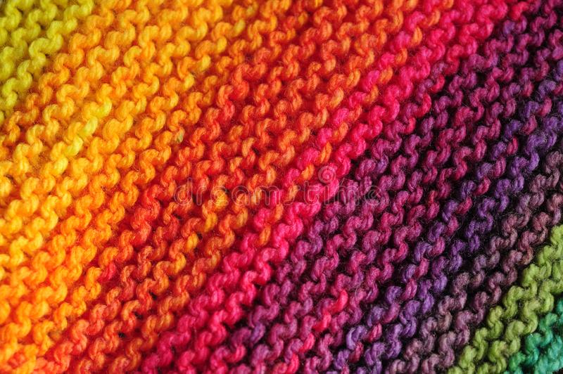 Close up of seamless knitted diagonal patterns in vivid rainbow mixed colors. Fragment of handmade seamless knitted patterns in joyful rainbow colors. Realistic stock images