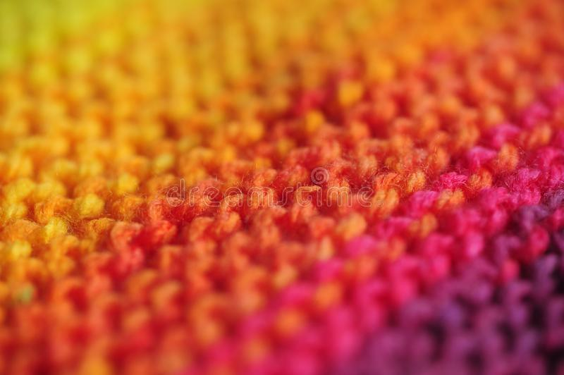 Close up of seamless knitted diagonal patterns in vivid rainbow mixed colors with shallow selective focus. Close up of handmade seamless knitted diagonal royalty free stock photo