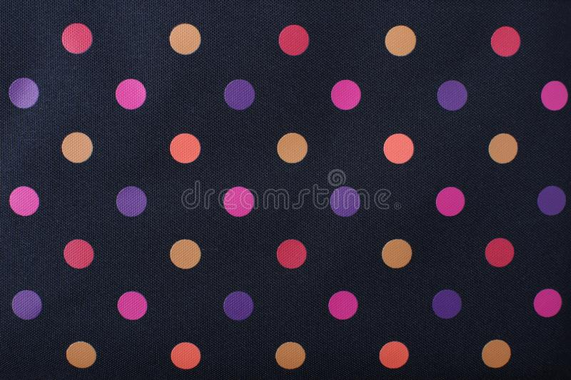 Close-up seamless texture background of colorful polka dots pattern on a black textile background. stock image