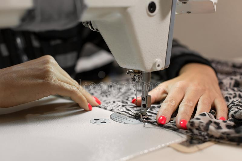Close up seamstress hand stitches fabric on the sewing machine royalty free stock images
