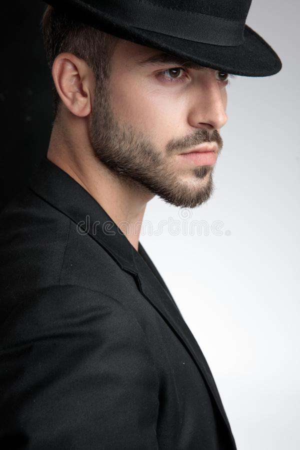 Close up of seductive young man wearing black hat royalty free stock photography