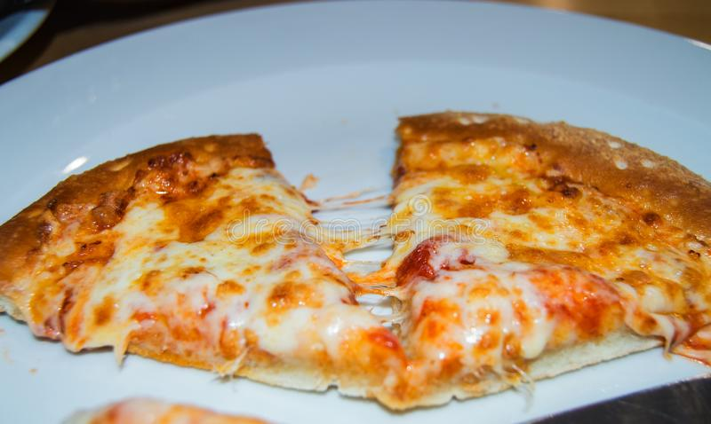 Close-up of selective focus, two pieces of hot pizza with cheese stretching on a white plate in a cafe on a wooden table stock photo