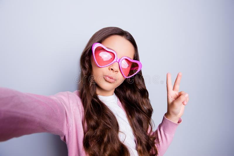 Close up self-portrait of pretty little girl making selfie gesturing peace symbol in casual clothes and heart-shaped glasses. While standing over grey stock images