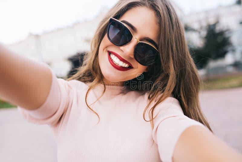 Close-up selfie-portret van aantrekkelijk meisje in zonnebril met lang kapsel en sneeuwwitte glimlach in stad royalty-vrije stock fotografie