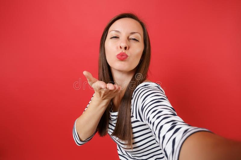 Close up selfie shot of pretty young woman in casual striped clothes blowing kisses send air kiss isolated on bright red stock image