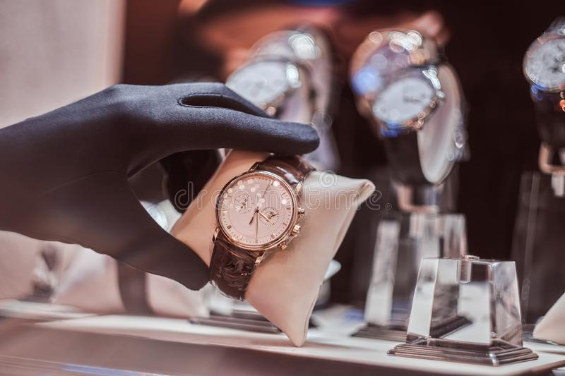 Close-up of the seller`s hand in gloves shows the exclusive men`s watch from the new collection stock photos