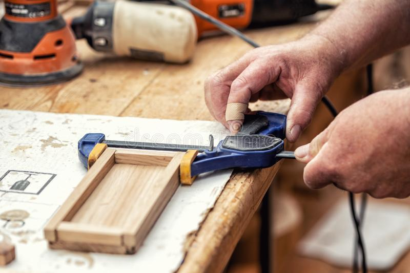 Close-up senior carpenter glueing wooden craft surface and joining with clamps. Woodwork carpenter with equipment and tools at stock photo