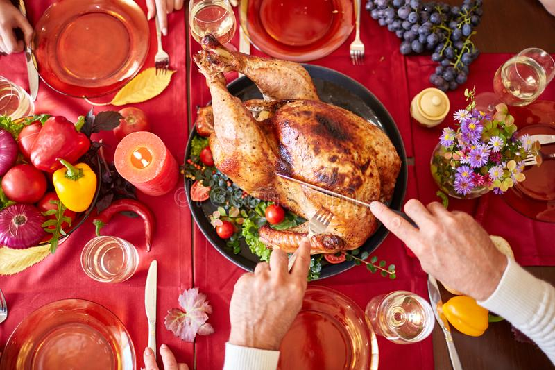 Close-up old man serving roasted turkey on a table background. Thanksgiving dinner. Traditional festive food concept. stock image