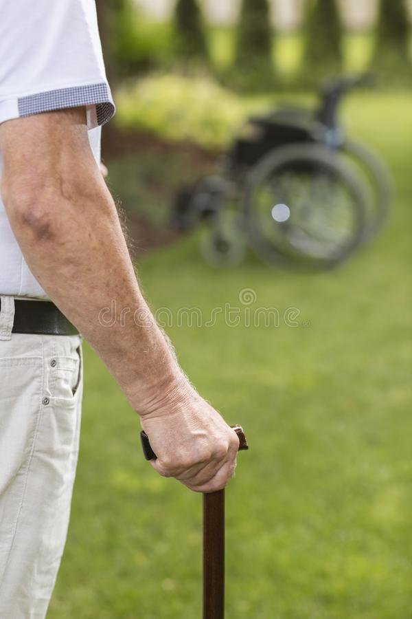 Close-up of senior man with walking stick while relaxing in the stock photo
