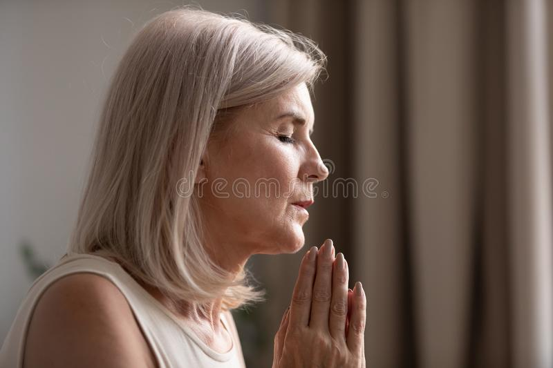 Close up of senior woman believer praying at home stock photography