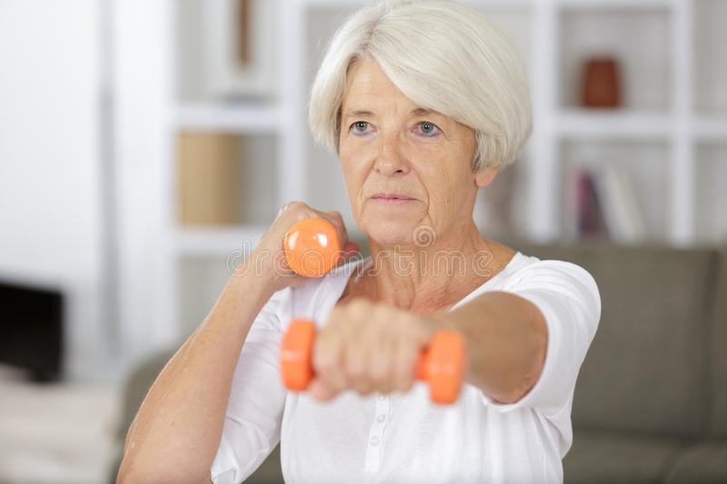 Close up senior woman exercising with dumbbell stock images