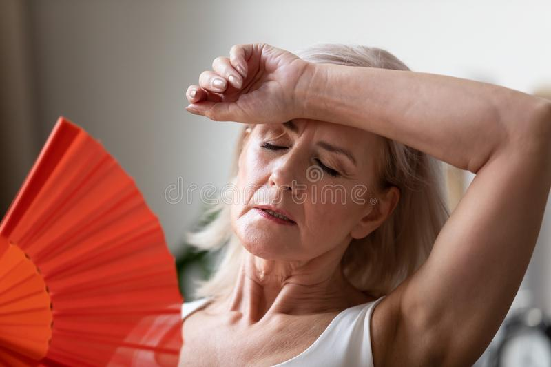 Close up of senior woman suffering from heatstroke at home stock photography
