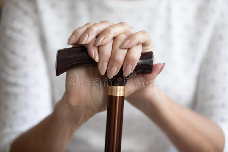 Close up mature woman holding hands on walking stick, cane royalty free stock image