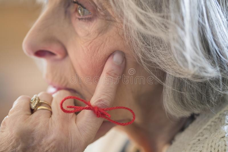Close Up Of Senior Woman With String Tied Around Finger As Reminder royalty free stock images