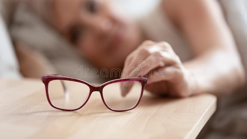 Close up of senior woman take glasses form bedside table royalty free stock image