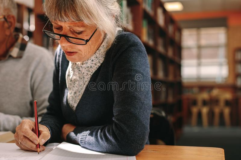 Close up of a senior woman writing in her book royalty free stock images