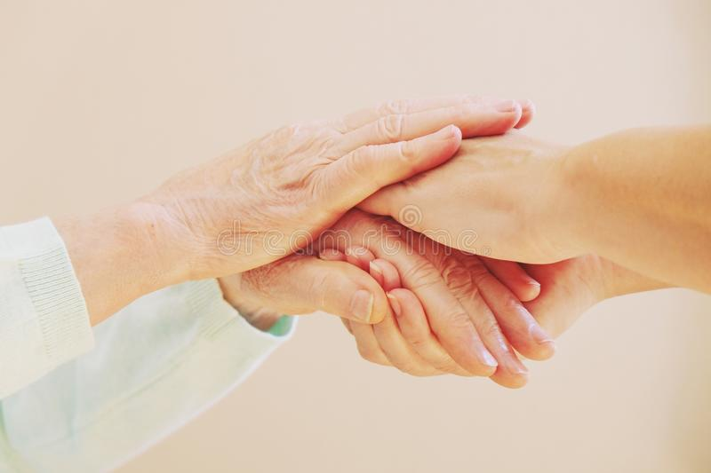 Close up of senior woman and young woman holding hands. Care and support concept stock images