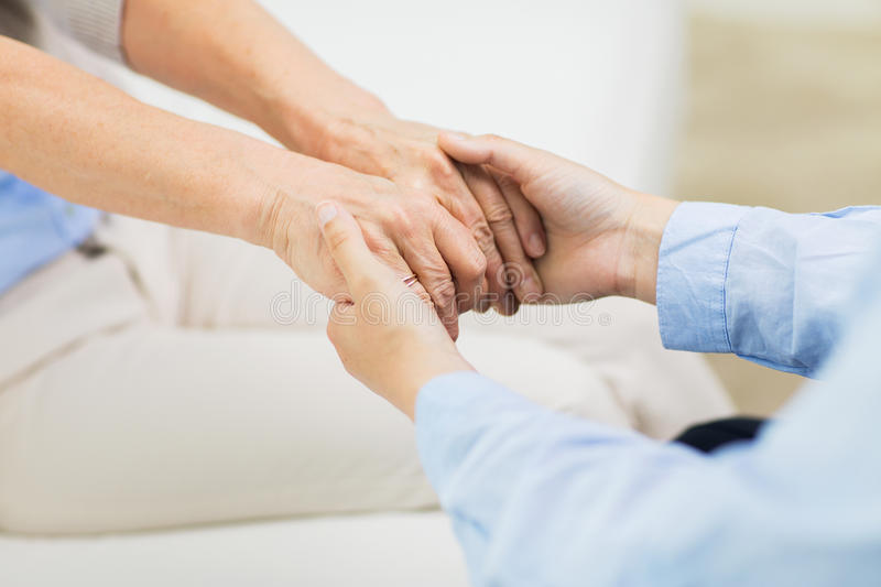 Close up of senior and young woman hands. People, age, family, care and support concept - close up of senior and young women holding hands stock photos