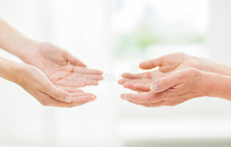 Close up of senior and young woman hands. People, age, family, care and support concept - close up of senior women and young women reaching hands out to each royalty free stock photos