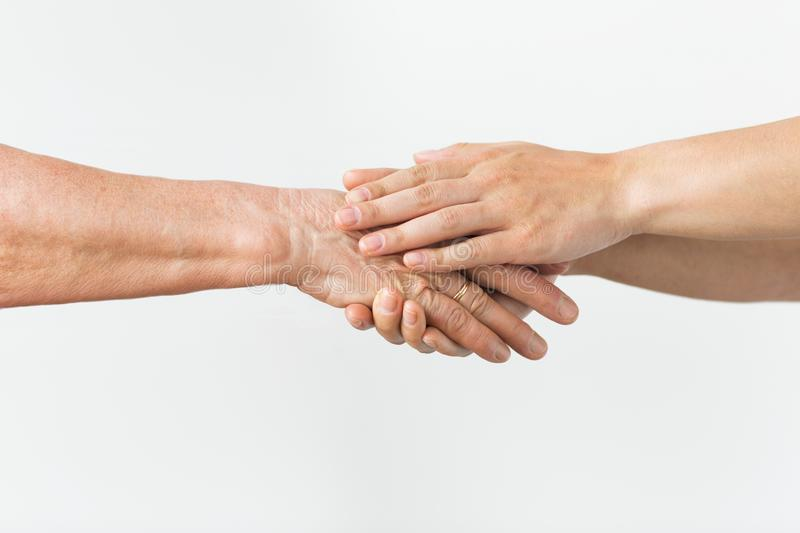 Close up of senior and young woman holding hands. People, age and body parts concept - close up of senior and young woman holding hands stock photography