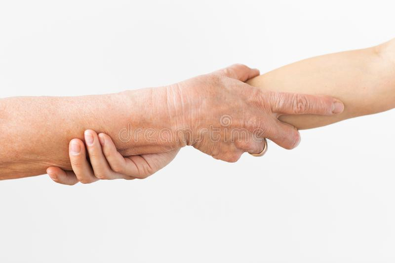 Close up of senior and young woman holding hands. People, age and body parts concept - close up of senior and young woman holding hands stock photos