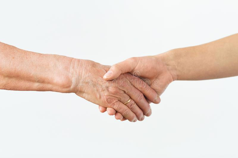 Close up of senior and young woman holding hands. People, age and body parts concept - close up of senior and young woman holding hands royalty free stock photography