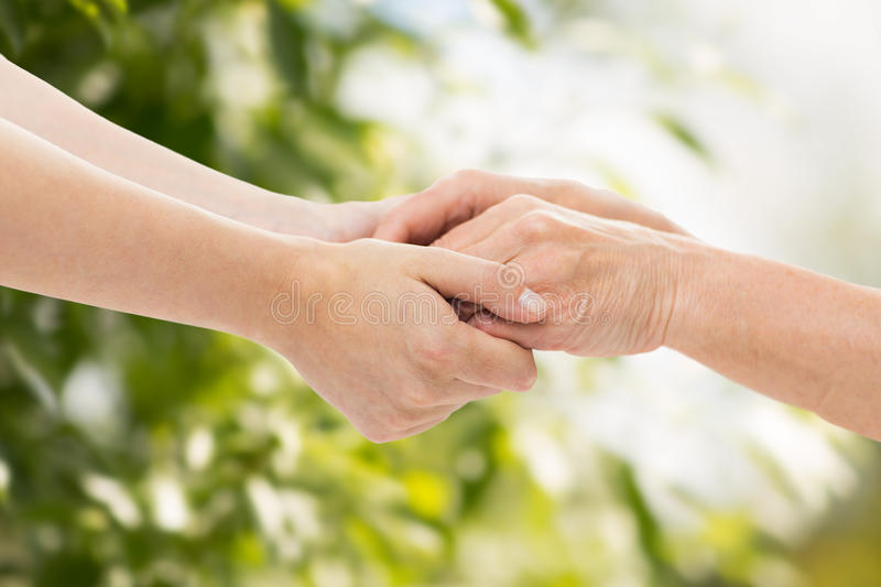 Close up of senior and young woman holding hands. People, age, family, care and support concept - close up of senior women and young women holding hands over royalty free stock photography