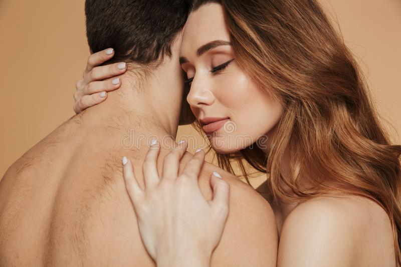 Close up of a sensual loving shirtless couple embracing stock photography