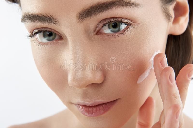 Close up sensual woman with cream on cheek royalty free stock photos
