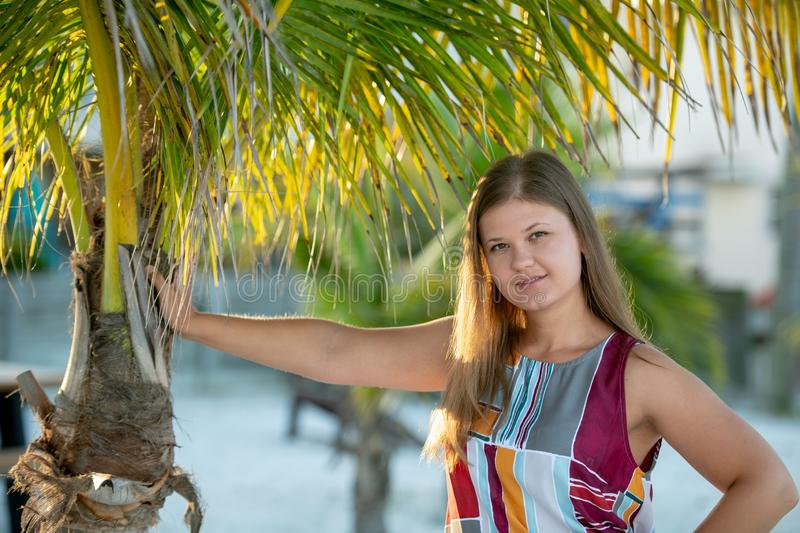 Close-up of sensual young woman with palm trees. Beach holidays woman wearing dress smiling on tropical beach summer vacation under the palm tree royalty free stock photos