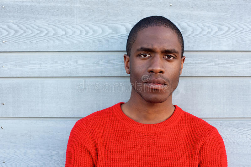 Close up serious black guy in red sweater stock photography