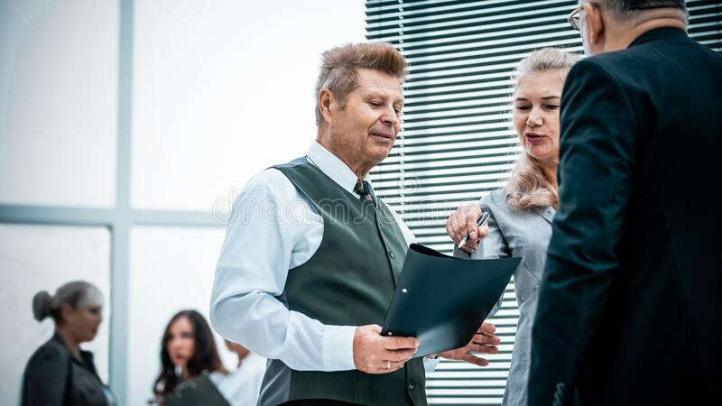Close up. serious employees discuss something standing in the office. royalty free stock image
