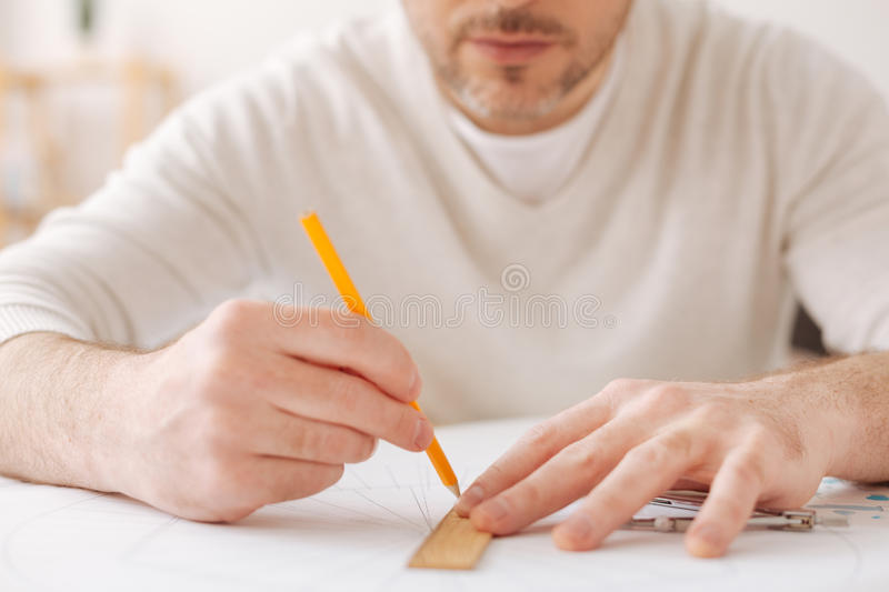 Close up of serious man that working at interesting sketch. Straight line. Attentive male person pressing lips and holding pencil in right hand while making royalty free stock images