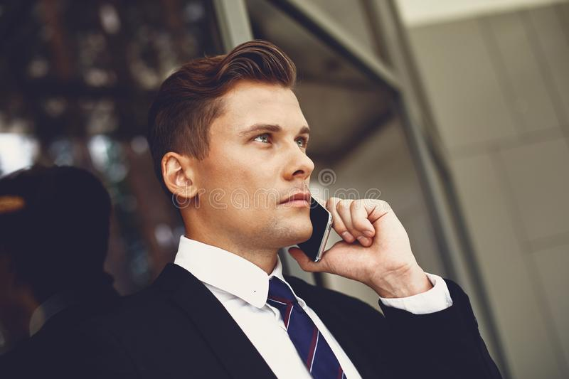Close up of serious young man in black suit talking on the phone royalty free stock photo
