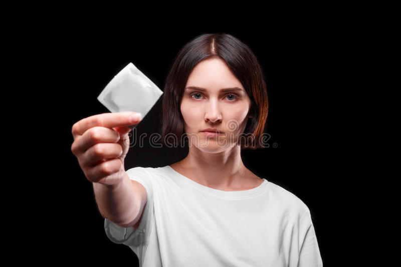 Close-up of a serious young woman showing a packed condom on a black background. Healthy lifestyle concept. Copy space. stock image