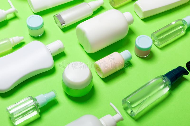 Close-up set of diffrent sized bottles and jars for cosmetic products on green backgound. Face and body care concept with copy. Space stock photos