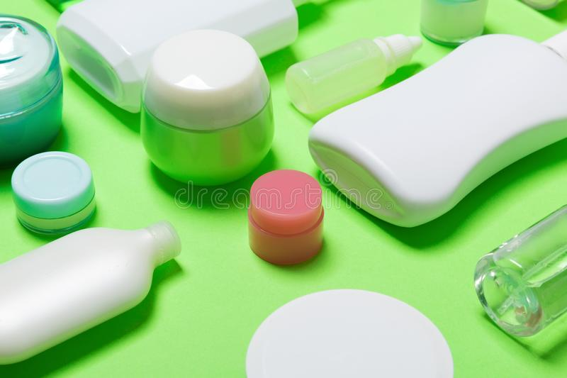 Close-up set of diffrent sized bottles and jars for cosmetic products on green backgound. Face and body care concept with copy. Space royalty free stock image