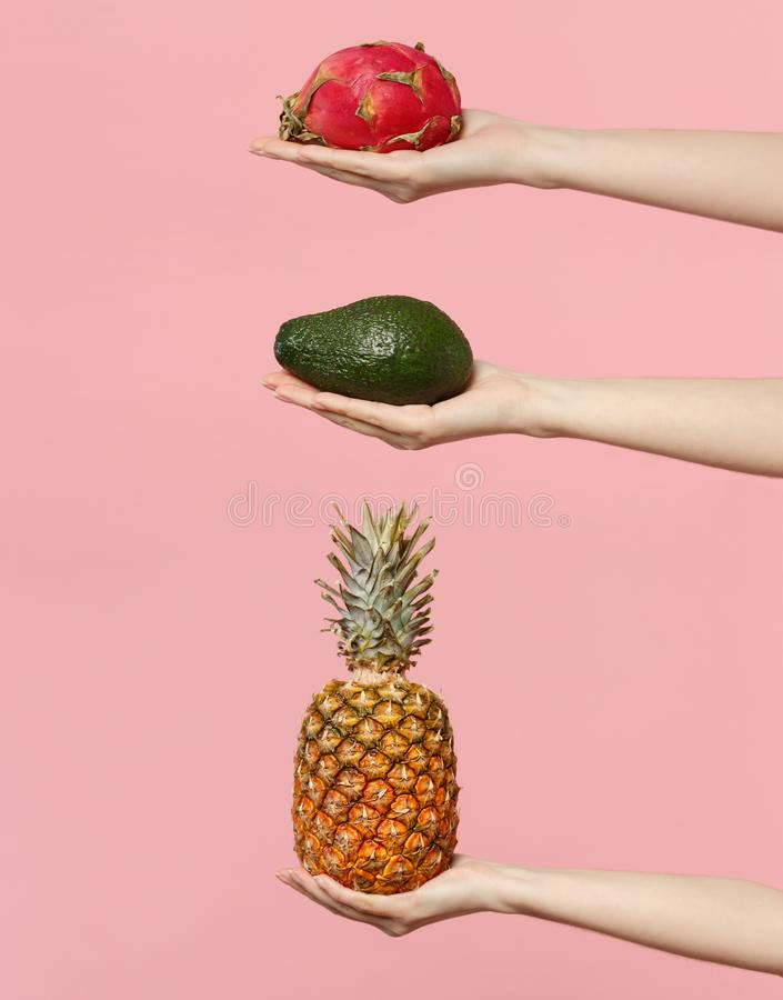 Close up set female hold in hand fresh green avocado pineapple pitahaya, dragon fruit isolated on pink pastel wall. Background. Copy space advertising mock up stock photo
