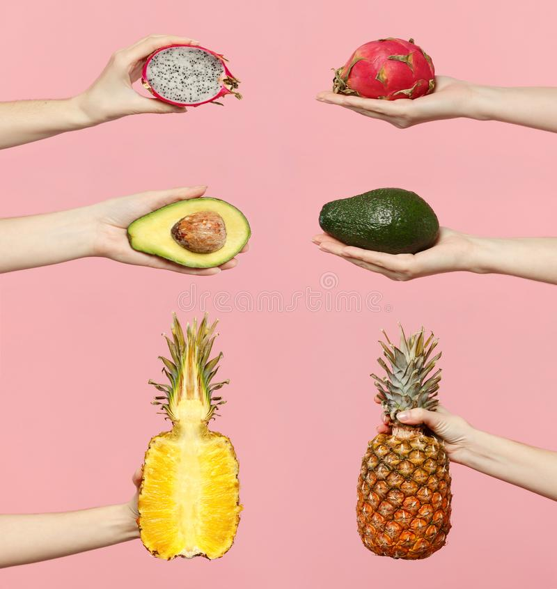 Close up set female hold in hand fresh half green avocado pineapple pitahaya, dragon fruit isolated on pink pastel wall. Background. Copy space advertising mock stock photography