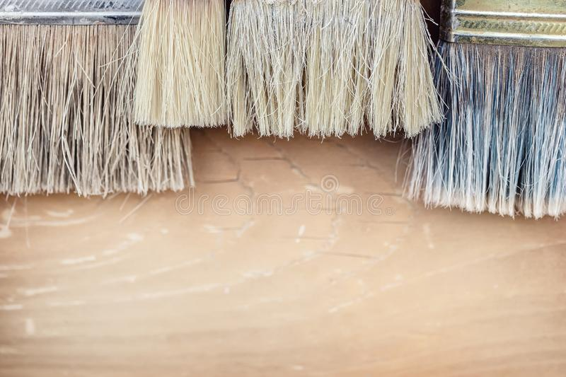 Close-up set of old used pant brushes on rustic wooden background. Vintage dirty paintbrushes royalty free stock image